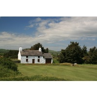 An old white building sits behind the 10th hole at Pwllheli Golf Club.
