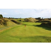 The ninth green at the Island Golf Club is tucked into the dunes.