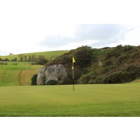 The 14th hole on the Druids Heath golf course is a par 3 surrounded by gorse and rocks.
